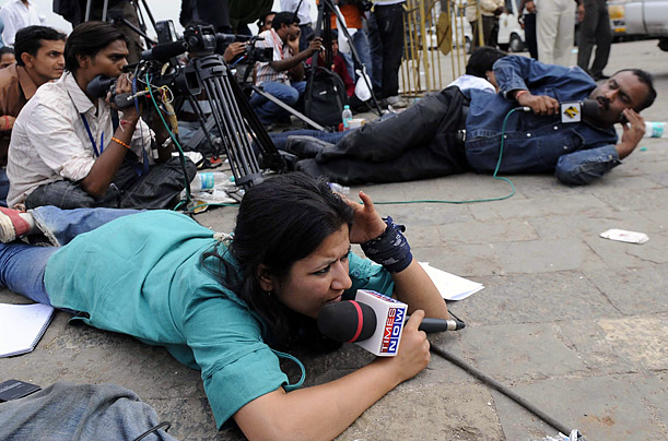 Journalists reporting on the terrorist attacks in Mumbai, keep low to the ground to avoid stray bullets.