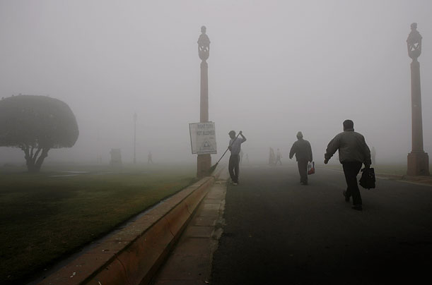 People walk to work in the morning fog in New Delhi, as a cold wave and dense fog hit the Indian capital and parts of north on Monday.