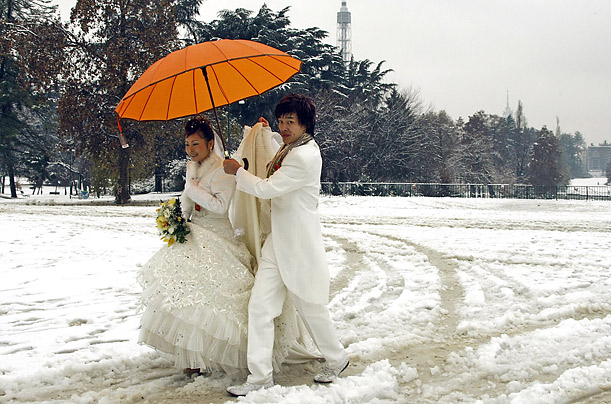 A newlywed couple trudges through the snow in Milan, Italy after the north of the country was hit by an unusually large snowfall.