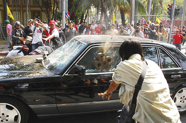 Protesters in Bangkok, Thailand throw rocks at a car coming out of parliament after a voting on the country's prime minister