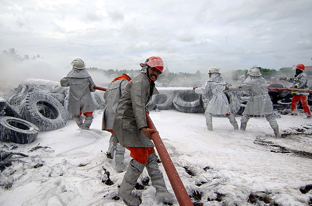 Members of a rescue team extinguish fire during an emergency landing drill