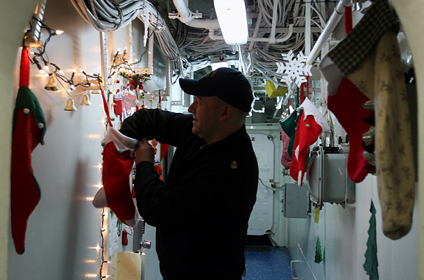 U.S. Navy Chief Petty Officer Scott Boyle, reaches into a Christmas stocking sent from American schoolchildren to sailors aboard the USS Iwo Jima, which is docked in Manama, Bahrain.