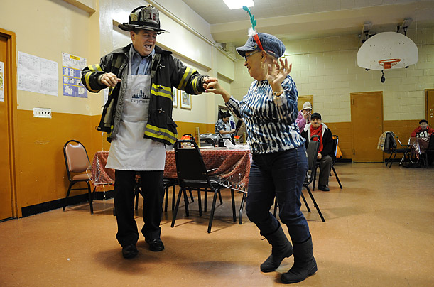 New York City Fire Department Captain Sean Giery dances with Helda DeJesus at the East Harlem Coalition of Senior Centers in New York. Captain Giery was participating in a Citymeals-on-Wheels program.