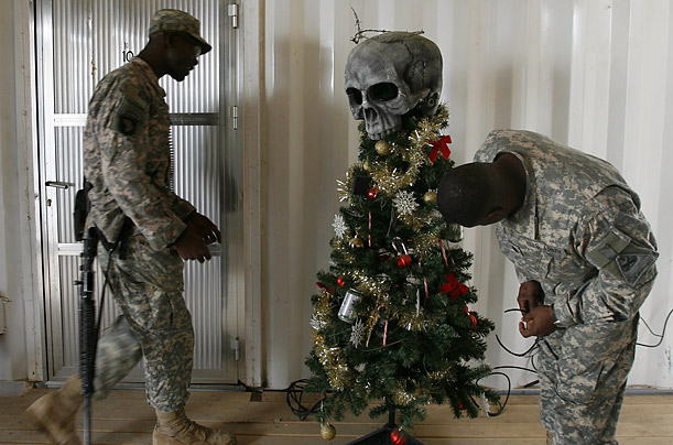 U.S. Soldiers from U.S. from the 1st Battalion, 6th Infantry place ornaments on their Christmas tree.