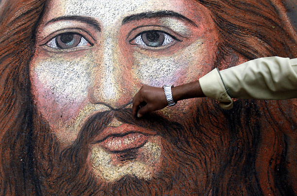 An Indian painter puts the finishing touches on a portrait of Jesus Christ in Kolkata.