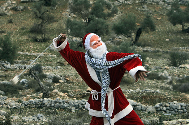 A Palestinian demonstrator dressed as Santa Claus uses a sling-shot to hurl stones at Israeli border police near the West Bank city of Ramallah.