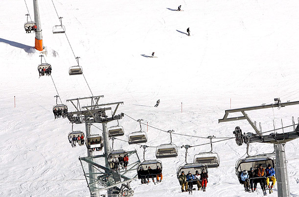 Skiers take the chairlift up the mountain at the Swiss mountain resort of Davos.