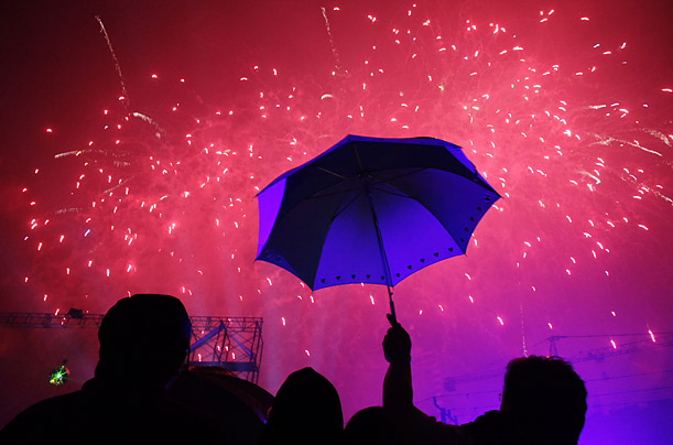 Spectators watch fireworks in the rain during a New Year's eve countdown in Fort  Manila, Phillipines.