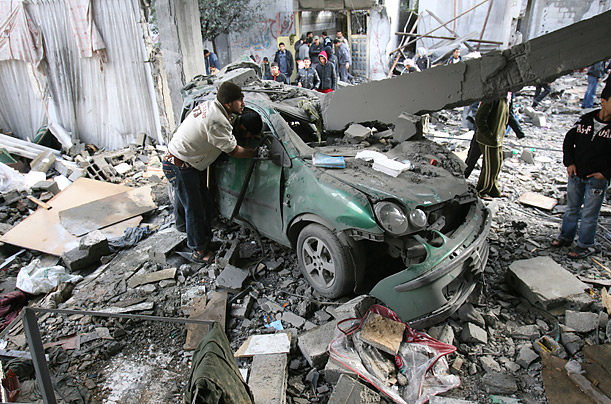 Palestinians inspect a destroyed building in the Jabalia refugee camp in Gaza, following overnight Israeli airstrikes.