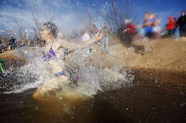 A man wearing a bikini enters the water during the Polar Bear Plunge and Arkansas River Scramble in Tulsa, Oklahoma.