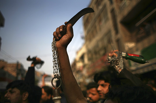Shiite Muslims hold knife blades on chains as they prepare to flagellate themselves during a Muharram procession in Lahore, Pakistan