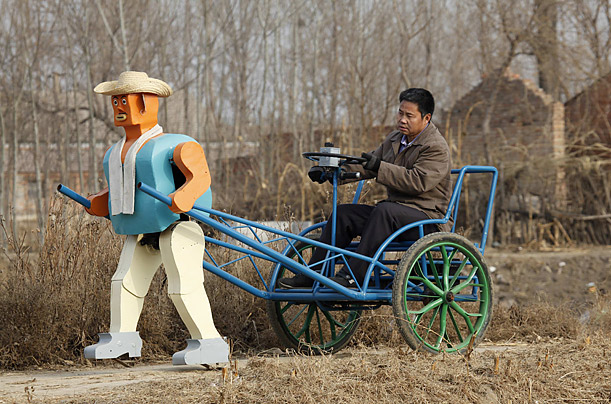 Farmer Wu Yulu drives his rickshaw with the help of his self-made walking robot, near his home in a village on the outskirts of Beijing.