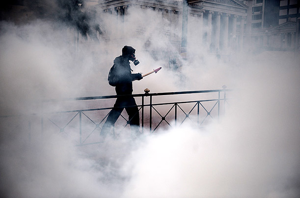 A student walks through tear gas in front of Athens University after a demonstration turned violent.