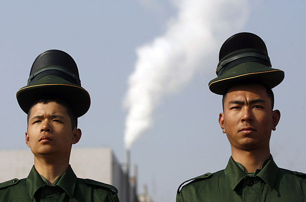 Paramilitary police recruits balance hats on their heads during a training session at a military base in China.