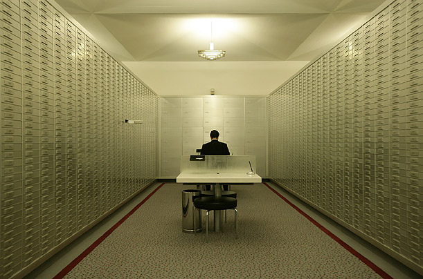 An employee sits amongst safe boxes before the public opening of the safe room of the Zuercher Kantonalbank in Zurich.