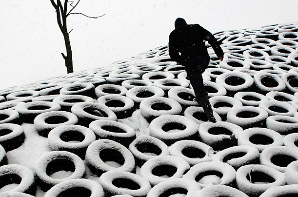 A farmer trudges through heavy snow storms in England.