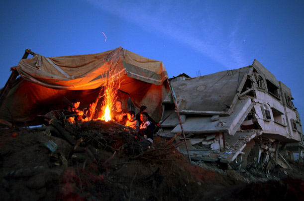 A Palestinian family sits around a campfire in the Gaza Strip.