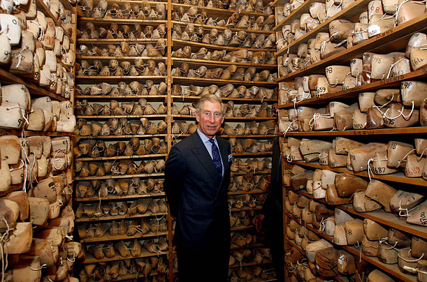 Britain's Prince Charles stands next to wooden lasts during a visit to a shoemaker's workshop in London.