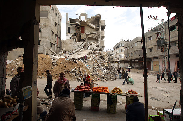 A grocer displays his wares outside his bombed shop facing a destroyed building in Gaza City.
