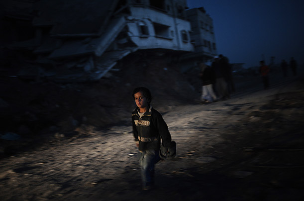A boy runs past a destroyed house in the Gaza Strip.