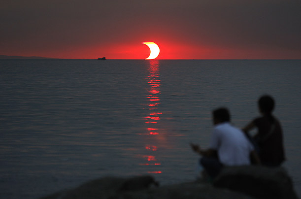 People watch a partial solar eclipse in Manila Bay, Phillipines.