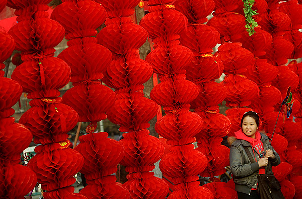 A tourist stands in front of lanterns at the Ditan Temple Fair during Chinese New Year celebrations in Beijing.