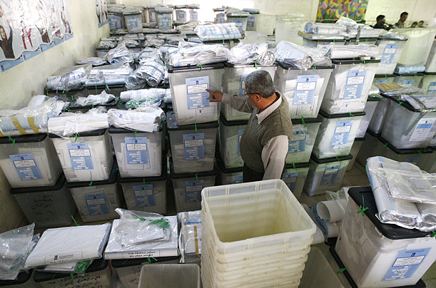 An Iraqi election official checks ballot boxes at a counting center in Baghdad after the close of polls on Sunday.