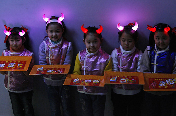 Children hold cards filled with New Year greetings as they wait for government officials to arrive at a community function for the upcoming Lantern Festival in Shanghai.