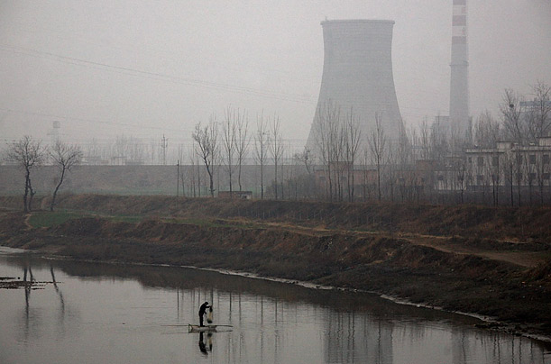 A fisherman stands in a small boat as he casts his net into a river near a power plant, in the town of Wulibao, China.