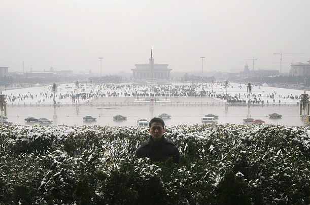 A plainclothes policeman stands guard at Beijing's Tiananmen Gate after a snowfall. China closed 12 highways around the capital on Thursday after a heavy snowfall was brought on after the clouds were seeded with chemicals.