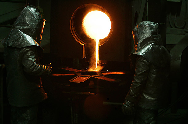 Workers are illuminated by the glow of freshly molten gold at the Minera Florida mine in central Chile.