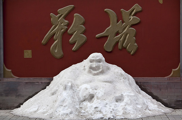 A snowman in the form of a laughing Buddha stands at the Pagoda of Tianning Temple in western Beijing.