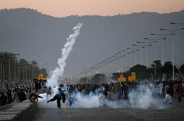 A Pakistani demonstrator throws back a tear canister launched by riot police during clashes in Islamabad.
