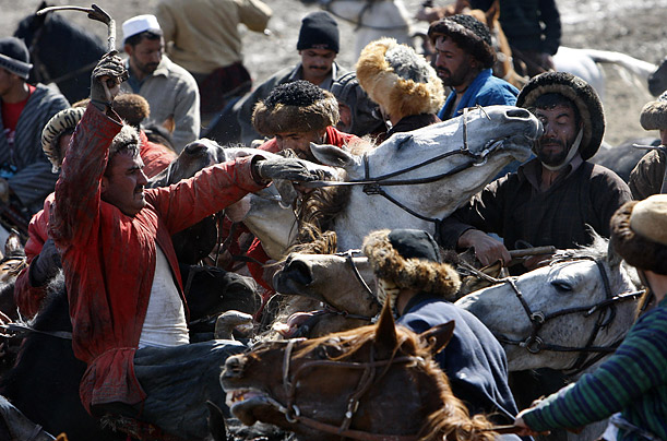 Men compete over a slaughtered sheep during a game of Bushkashi in Kabul, Afghanistan.
