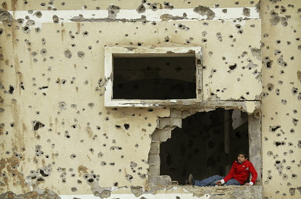 A Palestinian boy sits in the window of a bullet and shrapnel-riddled house in Rafah, southern Gaza Strip.