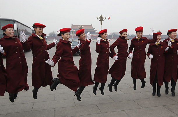 Hostesses pose for a picture at Tiananmen Square during the opening ceremony of the Chinese People's Consultative Conference in Beijing, China.