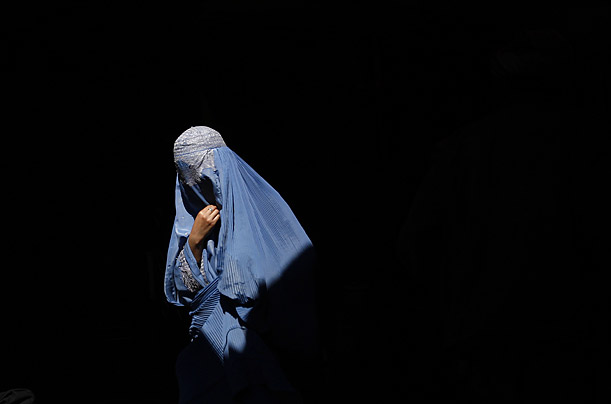 A burqa-clad Afghan woman walks in an old bazaar in Kabul, Afghanistan.