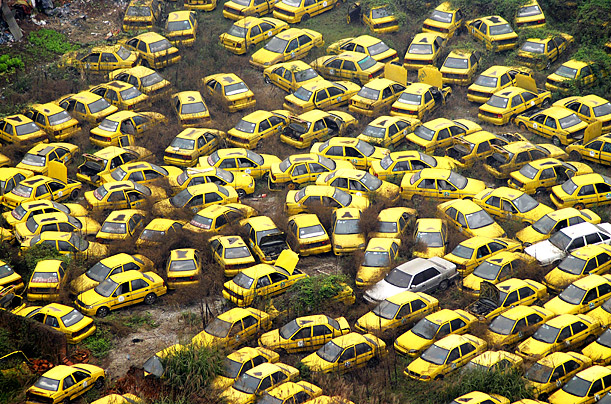 Numerous scrapped taxis litter a yard in the center of Chongqing, China.