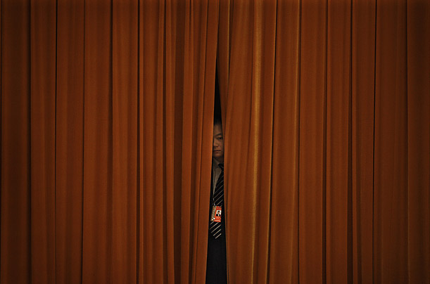 A Chinese security officer peeps through a curtain as Premier Wen Jiabao delivers his work reports at the opening session of the National People's Congress at the Great Hall of the People in Beijing.