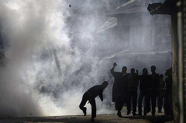 A Kashmiri Muslim protester throws a stone at Indian paramilitary soldiers and policemen as others shout slogans amidst tear gas