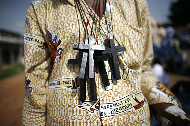 A man sells crosses to people waiting to catch a glimpse of Pope Benedict XVI on his visit to Cameroon.