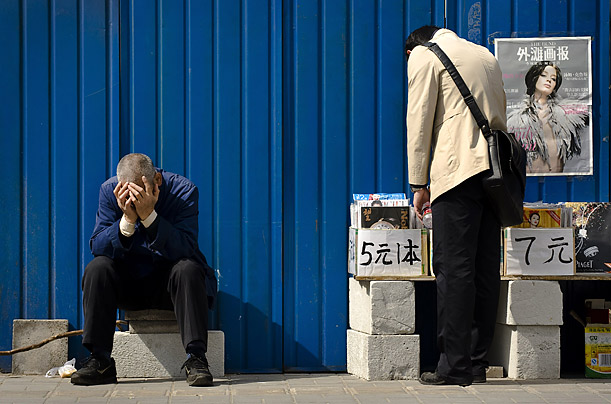 A Chinese man sits while another selects magazines on sale on a street in Beijing.