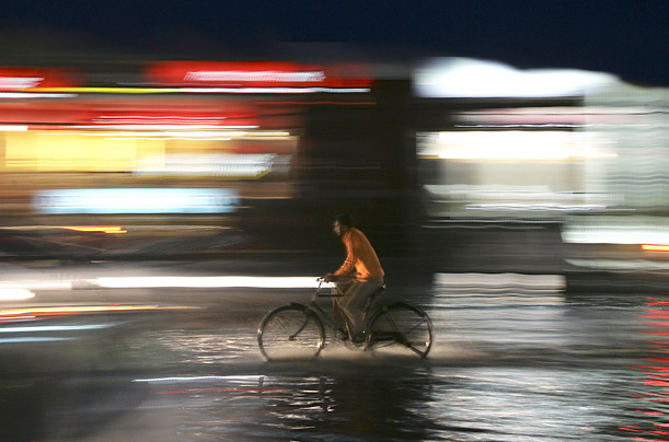 A man rides his bicycle through a waterlogged street during a heavy downpour in Amritsar, India.