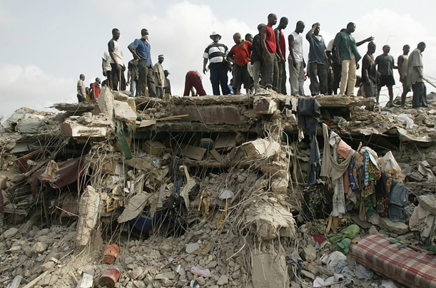 Rescue workers stand on the remains of a collapsed apartment building as they continue to search the rubble for survivors and victims in Lagos, Nigeria.