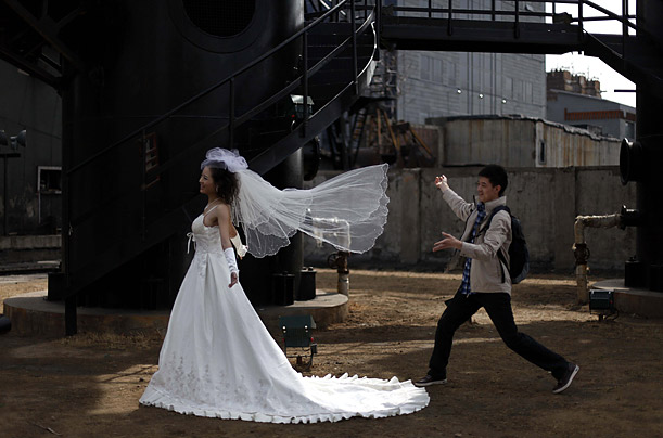 A wedding photographer's assistant prepares a Bride for a photoshoot in Beijing.