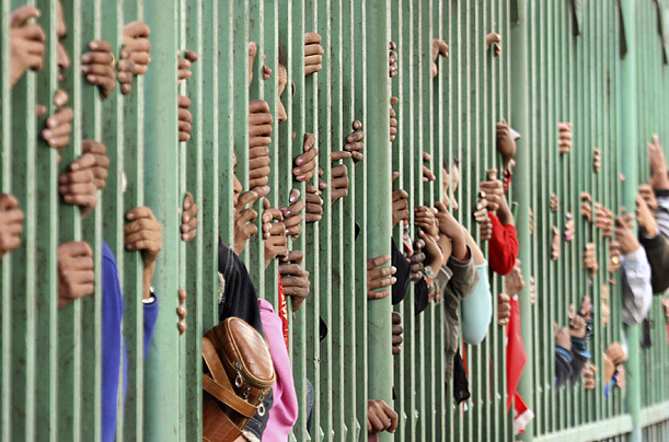 Spectators watch performances through a fence during a Nepalese cultural festival in Kathmandu.