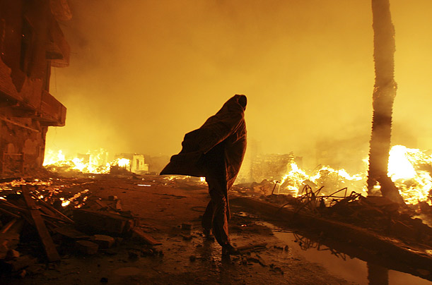 A man walks through Cairo's El Sharabia district where at least 13 people were injured in a rampaging fire.