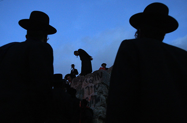 Ultra-Orthodox Hassidic Jews collect spring water for the Jewish rite of Mayim Shelanu at sunset in the Jerusalem mountains.