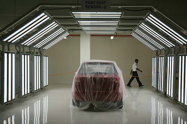 A worker walks past a vehicle on the assembly line at the newly inaugurated Volkswagen India Plant in Chakan, India.