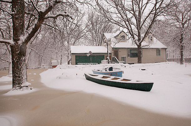 A canoe and boat sit in front of a flooded home near Moorhead, Minnesota.